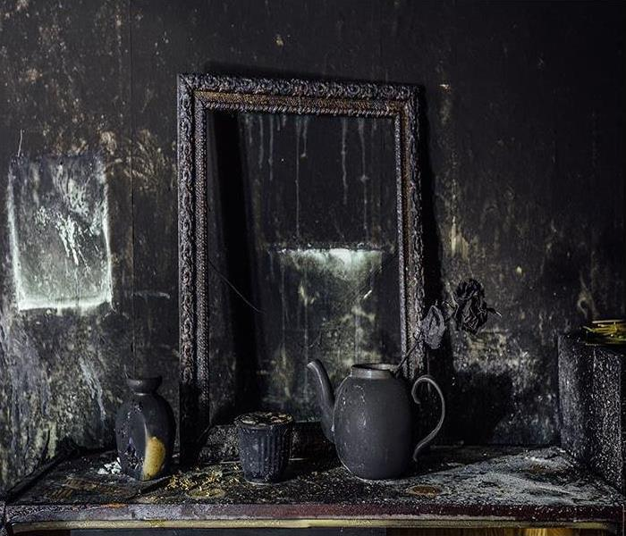 Charred wall, picture frame, and pot with burned rose covered in black soot