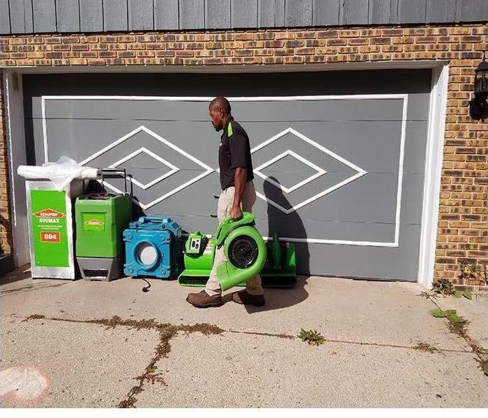 A technician outside a home holding an air dryer